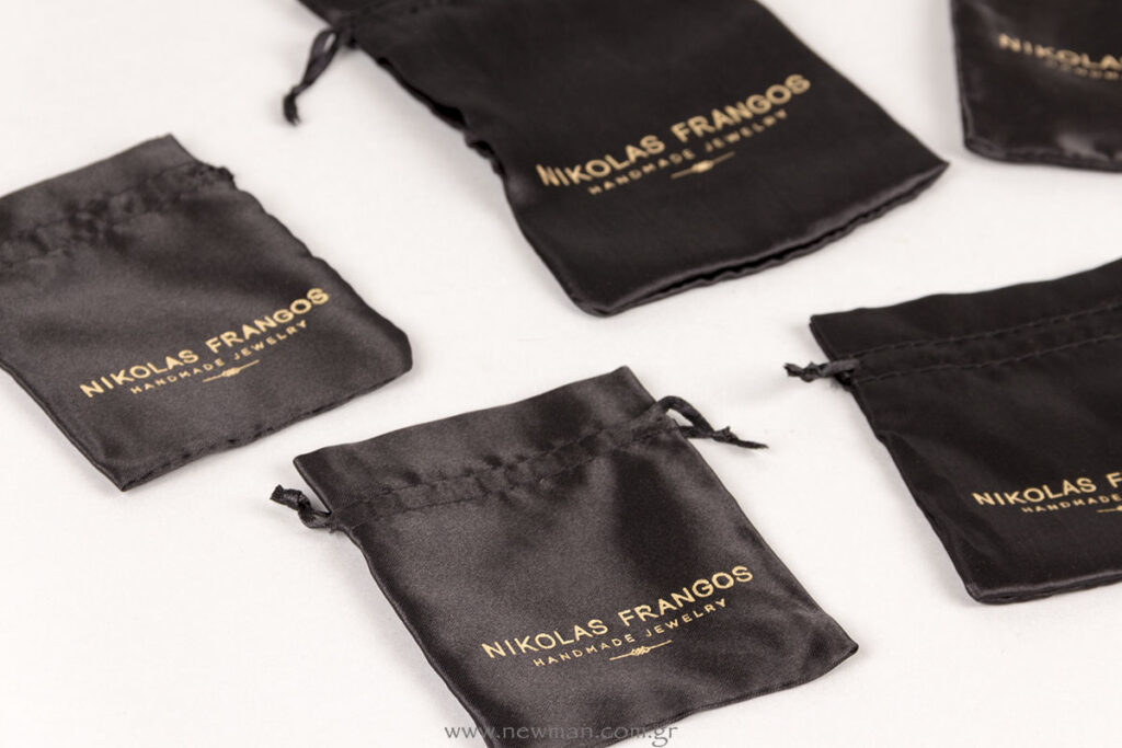Nikolas Frangos gold logo on black satin pouches