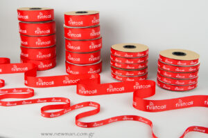We printed on embossed red grosgrain ribbon (two different weights) using silk-screen technique with white color.