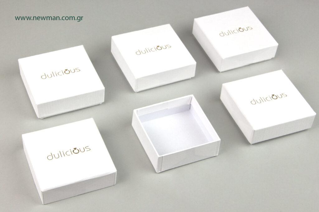 Εκτύπωση άσπρων κουτιών με το λογότυπο σε χρυσοτυπία.