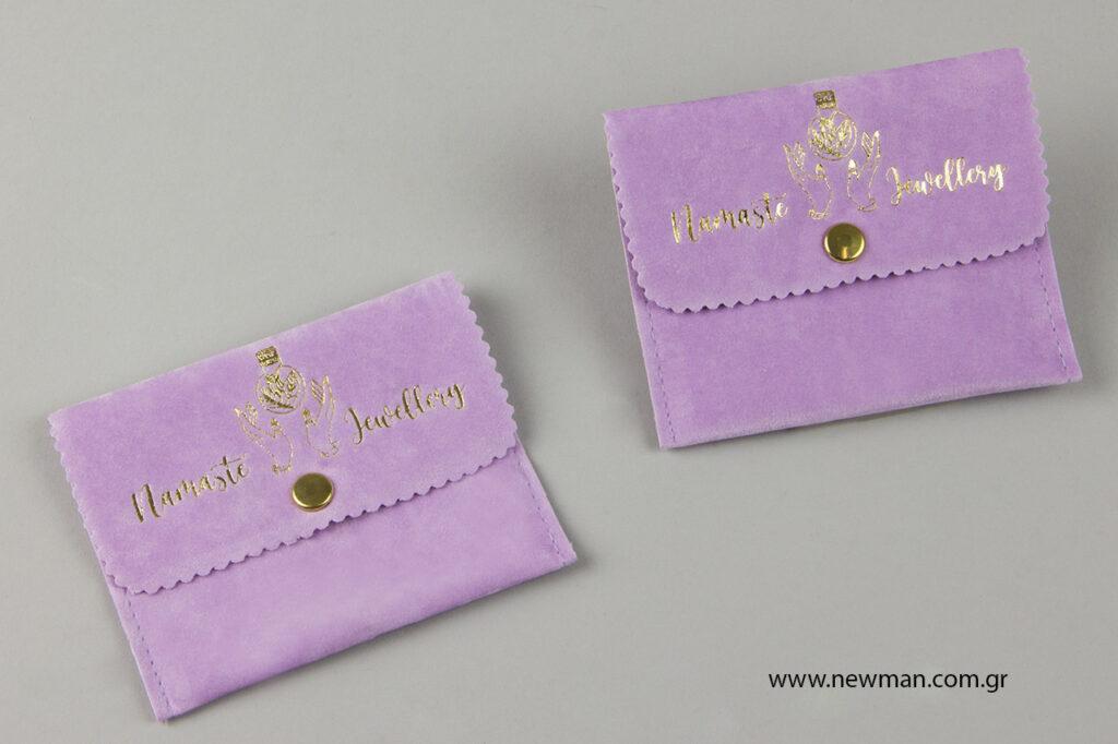 Σουέντ μώβ πουγκιά για κοσμήματα με χρυσοτυπία στο λογότυπο.