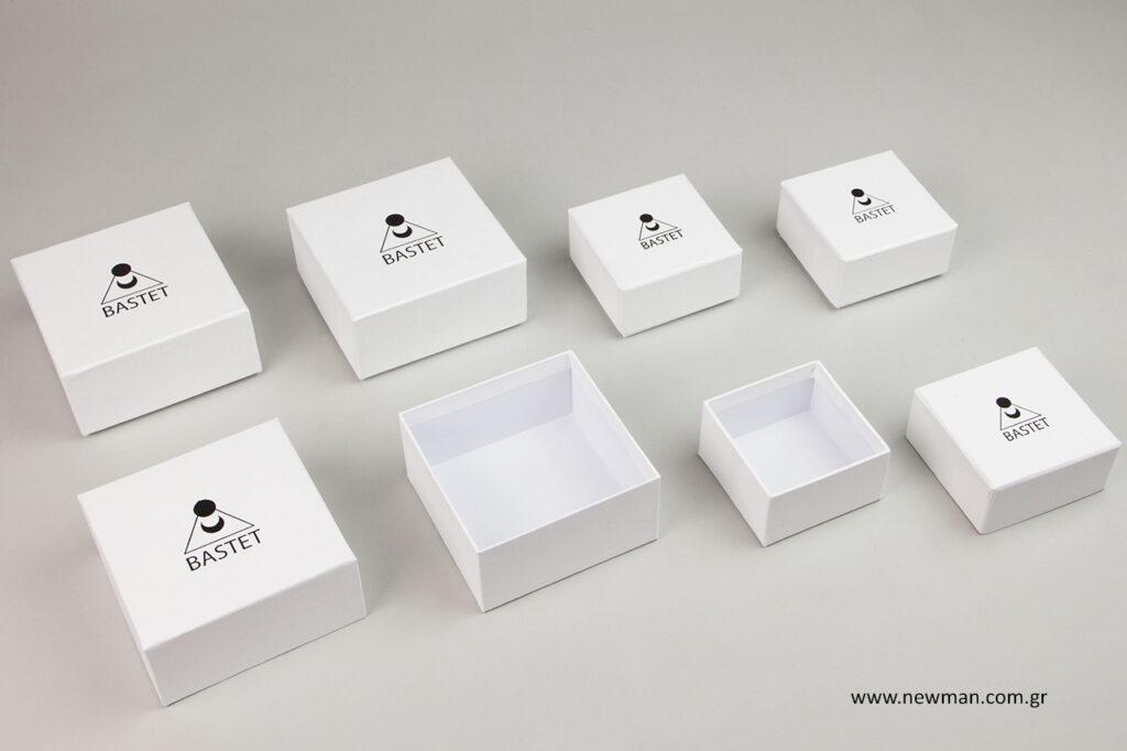 Tυπώσαμε με την ίδια τεχνική εκτύπωσης της μαύρης μεταλλοτυπίας την επωνυμία της εταιρείας (σύμβολο και όνομα) σε χάρτινα λευκά σαγρέ κουτιά με καπάκι.