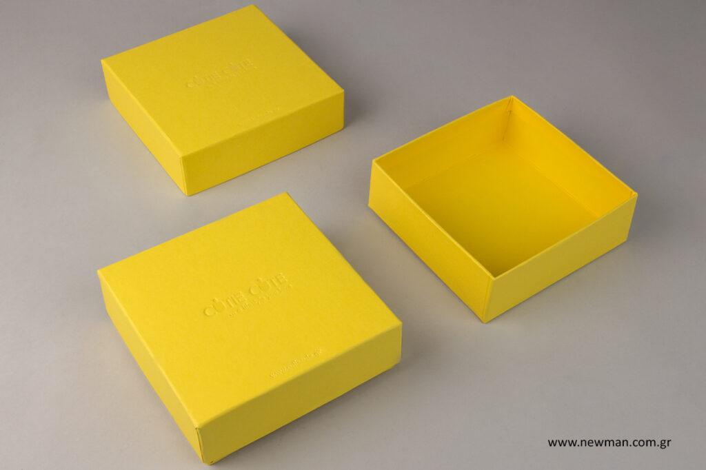 Το κουτί είναι ντυμένο κι απ'τις δύο πλευρές με κίτρινο χαρτί και τυπωμένο με διάφανη θερμοτυπία στο λογότυπο.
