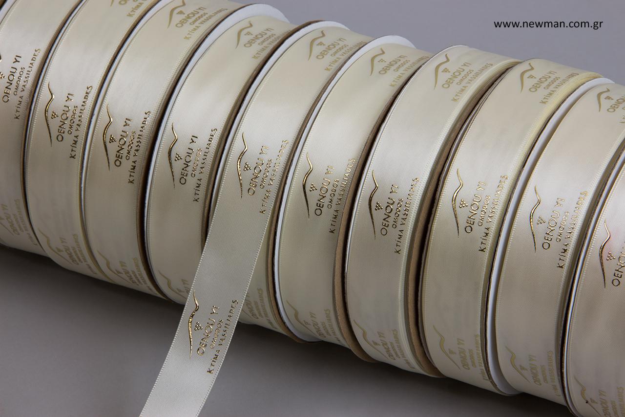 Πολυτελείας σατέν κορδέλα διπλής όψης σε εκρού χρώμα με ανάγλυφη μεταλλική χρυσή εκτύπωση.