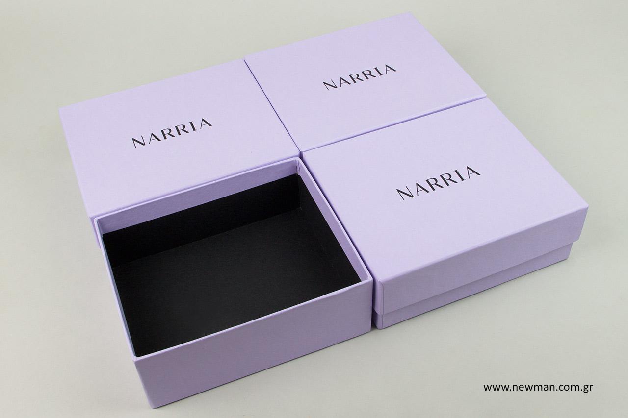 Λιλά κουτιά συσκευασίας με μαύρο εσωτερικό χαρτί.