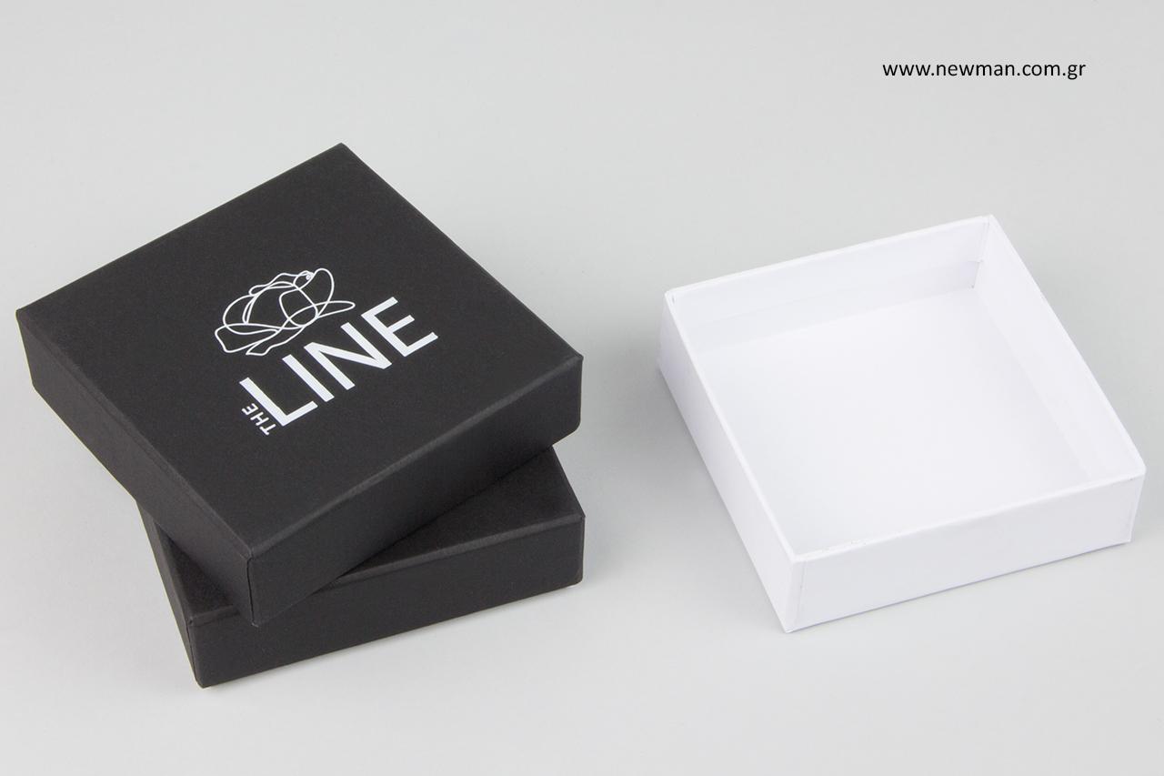 Κουτιά με λευκή βάση και μαύρο καπάκι.