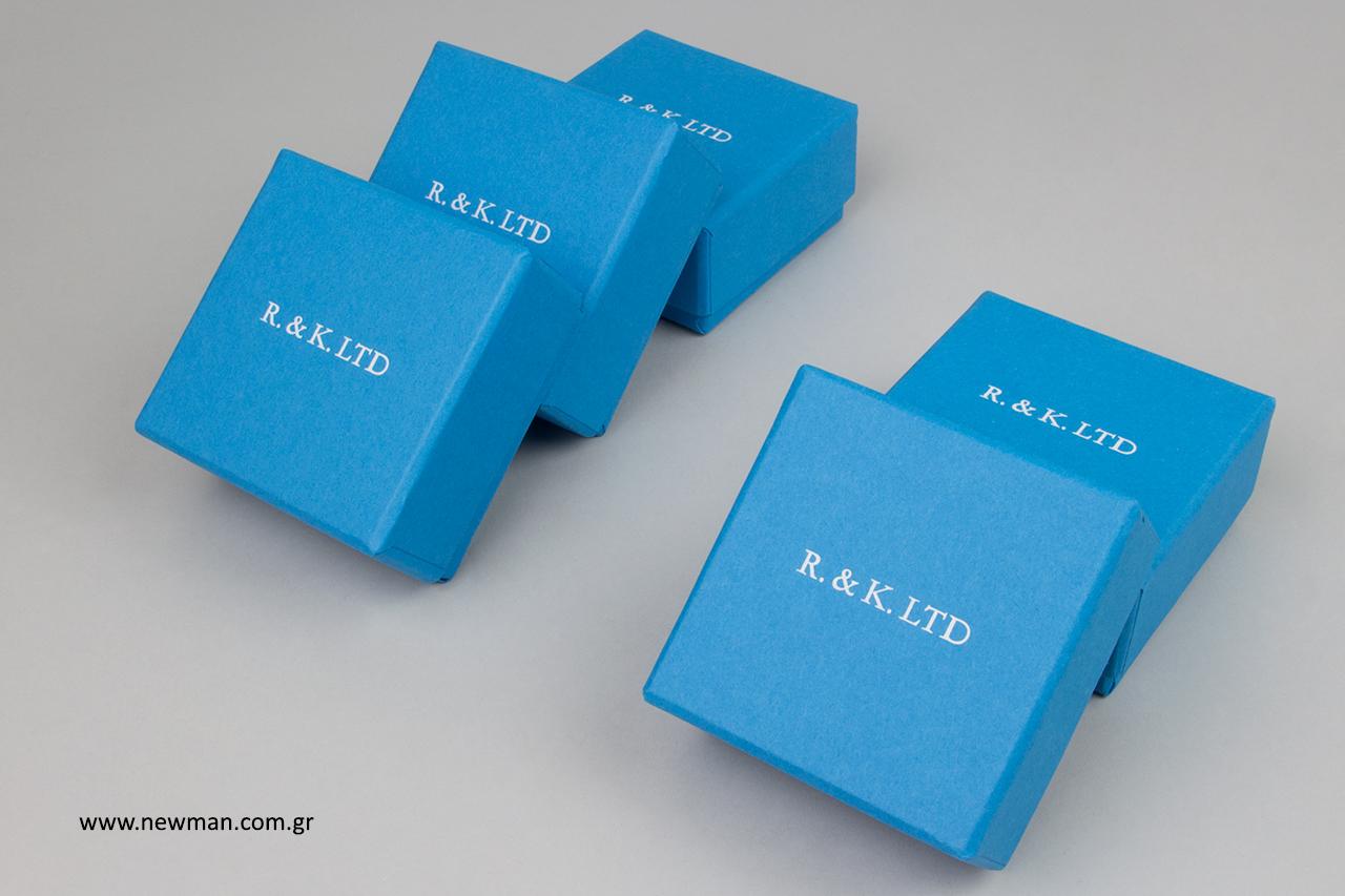 Λευκή μεταλλοτυπία σε μπλε επώνυμα κουτιά.